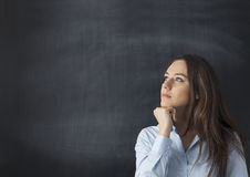 Thoughtful young woman on chalkboard background Stock Photos