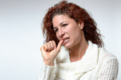Thoughtful young woman chewing her thumb nail Stock Images