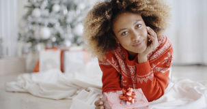 Thoughtful young woman with a Christmas gift Royalty Free Stock Images