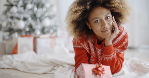 Thoughtful young woman with a Christmas gift Royalty Free Stock Image
