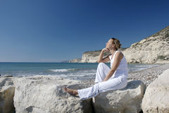 Thoughtful, young woman in coastal scene. Royalty Free Stock Photos