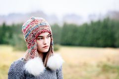 Thoughtful young woman in colorful woolen cap stock photography