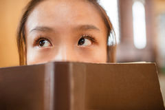 Thoughtful young woman cover her face with book Royalty Free Stock Photos