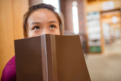 Thoughtful young woman covering her face with book Stock Photography