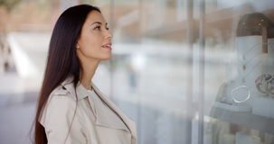 Thoughtful young woman eyeing shop merchandise Royalty Free Stock Photo