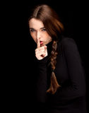 Thoughtful young woman with finger on mouths Royalty Free Stock Photography