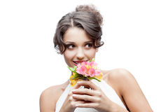Thoughtful young woman with flower in hair. Young attractive thoughtful caucasian woman with lily flowers in hand Royalty Free Stock Images