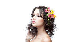 Thoughtful young woman with flower in hair. Young attractive thoughtful caucasian woman with lily flowers in hand stock image