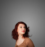 Thoughtful young woman gesturing with copy space. Pretty young woman gesturing with empty space Stock Image