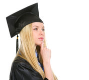 Thoughtful young woman in graduation gown Stock Images