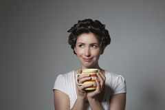 Thoughtful young woman with hair curlers holding cup Royalty Free Stock Photos