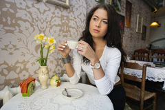 Thoughtful young woman having coffee at cafe Royalty Free Stock Image