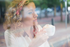Thoughtful young woman having coffee in cafe Stock Image