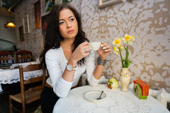Thoughtful young woman having coffee at cafe Stock Image