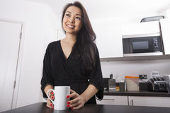 Thoughtful young woman having coffee in kitchen Stock Photography