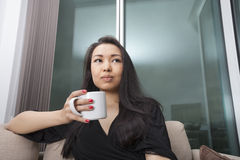 Thoughtful young woman having coffee in living room Stock Photography