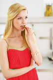 Thoughtful young woman having snack in kitchen Stock Photo