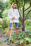 Thoughtful young woman with hoe. Working in the garden bed Stock Image