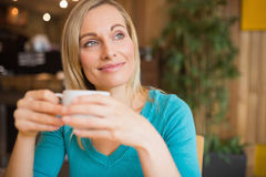 Thoughtful young woman holding coffee cup Royalty Free Stock Images