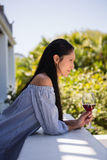 Thoughtful young woman holding red wine while standing in cafe Stock Images
