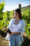 Thoughtful young woman holding wine bottle at vineyard Royalty Free Stock Photos