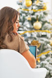 Thoughtful young woman with laptop in front of christmas tree Stock Images