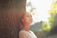 Thoughtful young woman lean against tree. In park royalty free stock photo