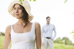 Thoughtful young woman looking away with man in background at park Stock Images