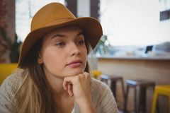 Thoughtful young woman looking away. Thoughtful beautiful woman looking away in cafe Stock Image