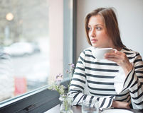 Thoughtful young woman looking out from window while drinking coffee in cafe Royalty Free Stock Photography