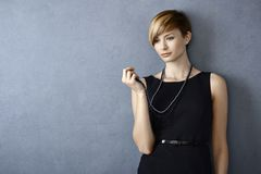 Thoughtful young woman looking at pearl necklace. Standing in front of grey wall Royalty Free Stock Photo