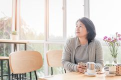 Thoughtful young woman looking through window at coffee shop. Lifestyle concept Royalty Free Stock Images