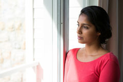 Thoughtful young woman looking through window. Thoughtful pretty woman looking through window at home Stock Photography