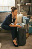 Thoughtful young woman with luggage and tablet pc Royalty Free Stock Photography
