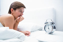 Thoughtful young woman lying in bed Stock Photo