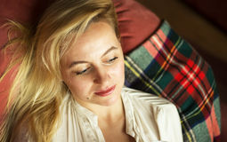 thoughtful young woman lying on sofa at home Stock Photography