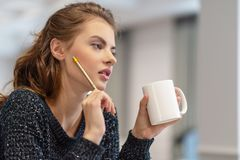 Thoughtful young woman making notes using notepad in kitchen stock images