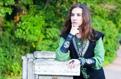 Thoughtful young woman in medieval suit Royalty Free Stock Image
