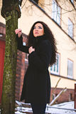 Thoughtful young woman near tree at street. Pretty woman in coat standing near tree on street Royalty Free Stock Image