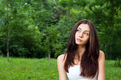 Thoughtful young woman outside in park Royalty Free Stock Photography