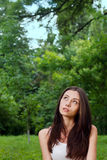 Thoughtful young woman outside in park. Portrait of a thoughtful young woman looking up  outside in park Royalty Free Stock Image