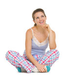 Thoughtful young woman in pajamas sitting on floor. And looking on copy space Royalty Free Stock Photo