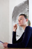 Thoughtful young woman with pen and notepad Royalty Free Stock Images