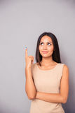 Thoughtful young woman pointing finger up Stock Photography