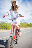 Thoughtful young woman posing while riding bike Stock Photos