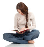 Thoughtful young woman reading book Stock Images