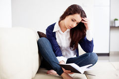 Thoughtful young woman reading a book at home Stock Image