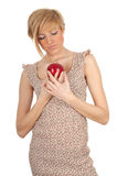 Thoughtful young woman with red apple Stock Photography