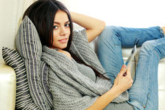Thoughtful young woman resting on a sofa with tablet computer Stock Photography