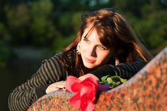 Thoughtful young woman with rose. Royalty Free Stock Image